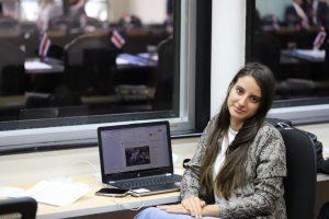 Cuban journalist Karla Pérez González sits next to a laptop