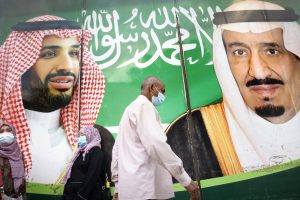 People wearing face masks walking past a banner of Saudi King Salman and Crown Prince Mohammed bin Salman
