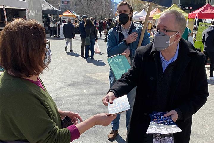 Scott Stringer handing a campaign flyer to a constituent