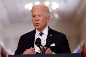 President Joe Biden stands at a lectern and places notes in his pocket