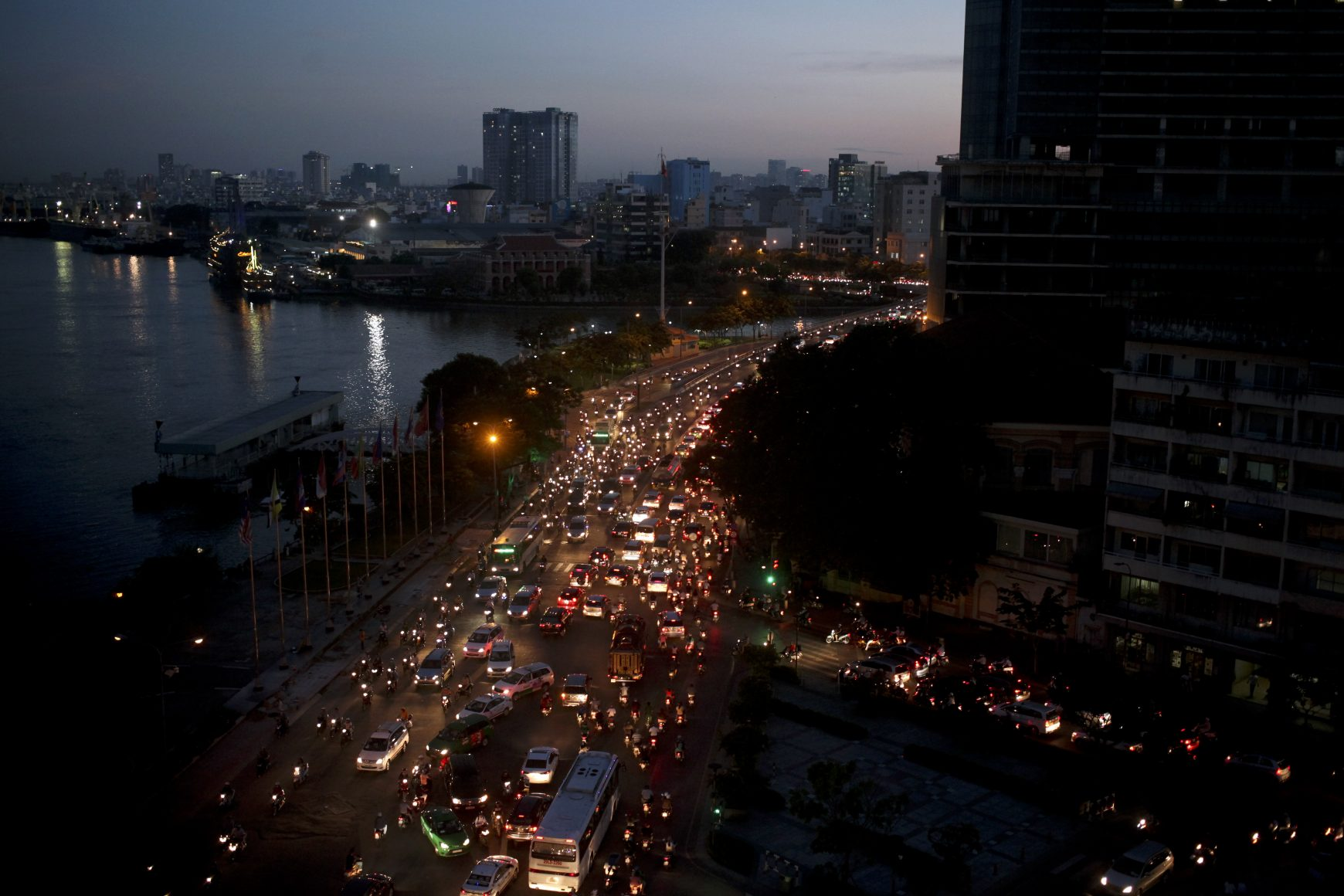 Traffic moves besides the Saigon river during rush hour in Ho Chi Minh City, Vietnam
