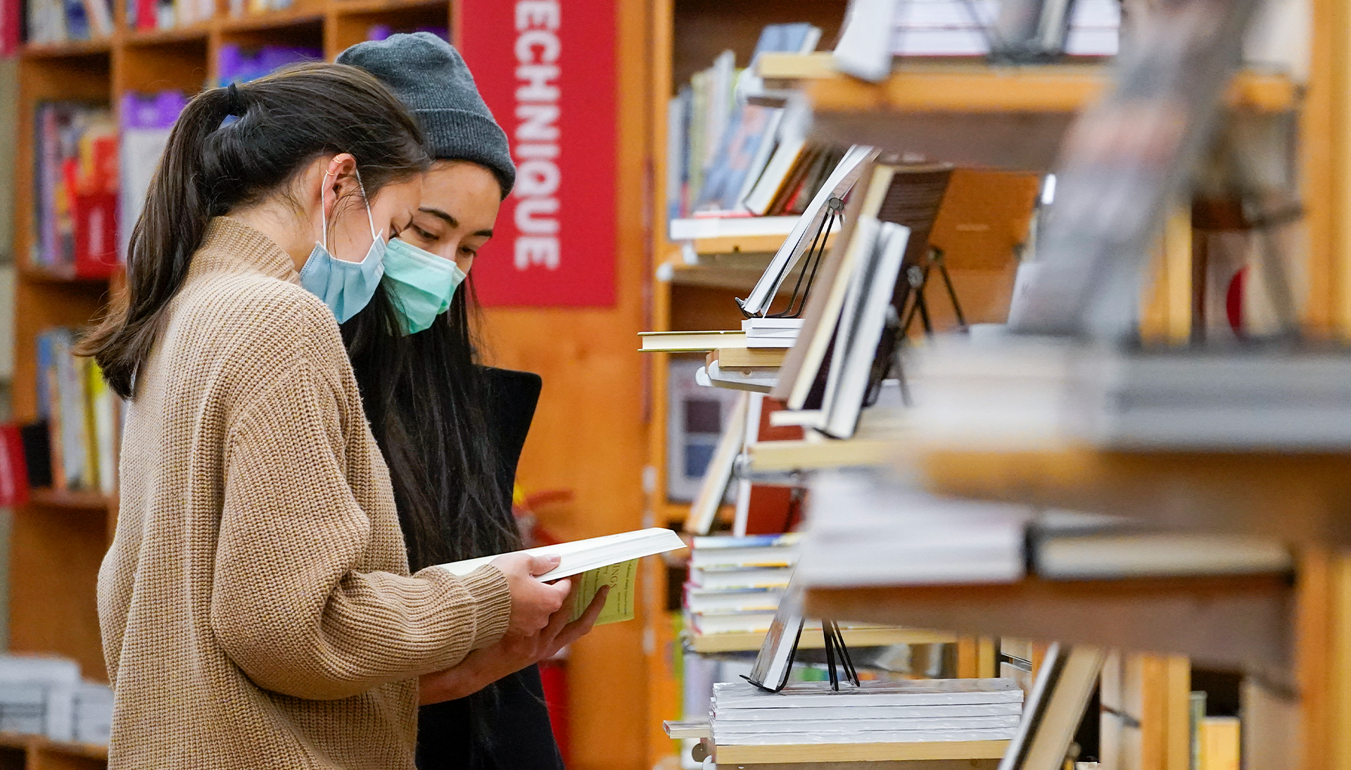 On left: two masked individuals looking down at books in a bookstore; books and bookshelves in background