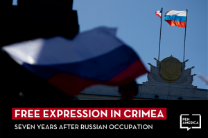 """Russian and Crimean flags fly over a local government building in Simferopol, Ukraine; on top, text reads: """"Free Expression in Crimea: Seven Years After Russian Occupation"""""""