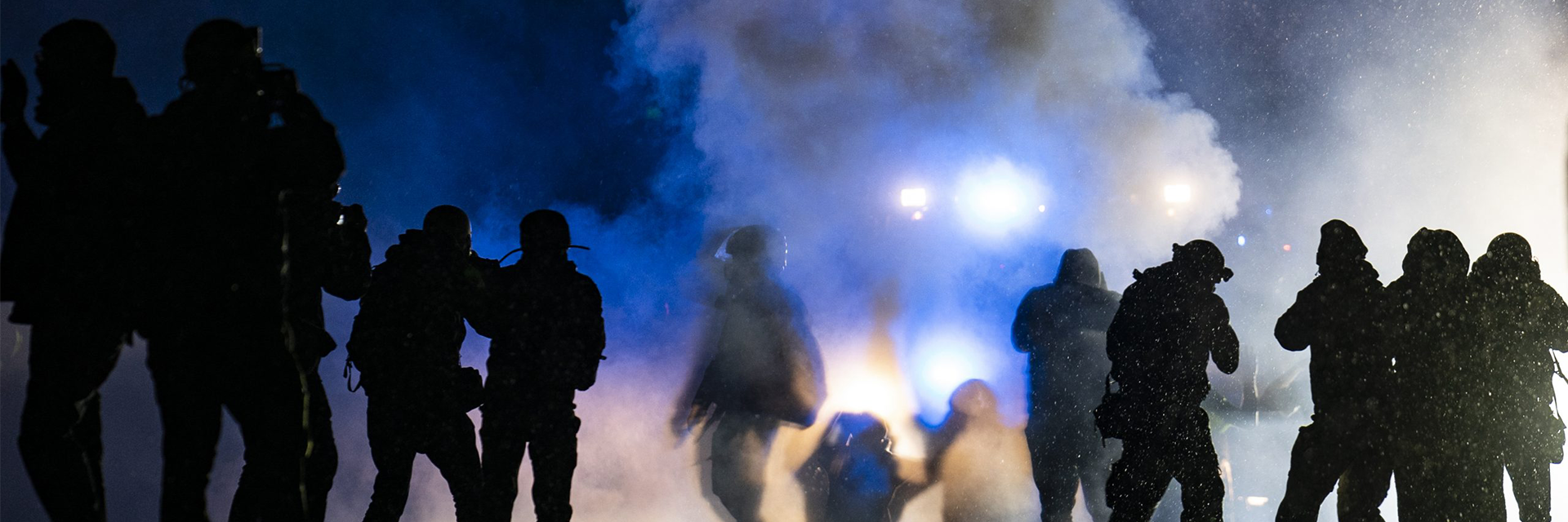 Shadows of demonstrators with tear gas in background