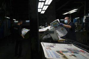 man holding copy of newspaper