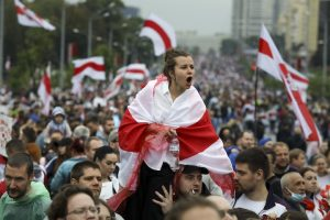 Opposition supporters in Minsk, Belarus; woman covered by an old Belarusian national flag in center