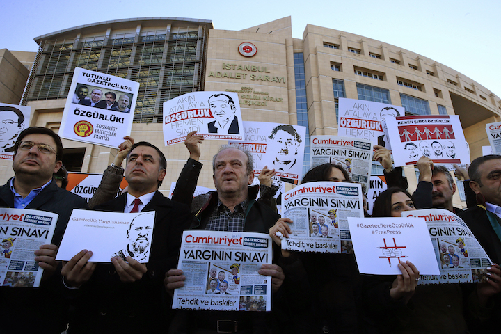 Demonstrators holding placards and copies of the Cumhuriyet daily newspaper at a protest