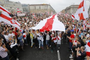 Demonstrators carrying an opposition flag at Independence Square in Belarus