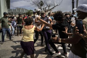 Crowd of protesters in Havana, Cuba, with one being detained by police