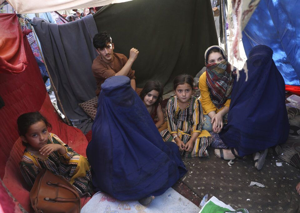 a group of Afghan women and children sit inside a tent