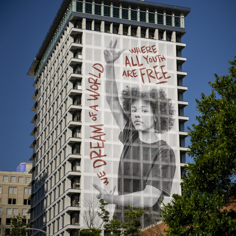 Photo of girl posing on a large scale public mural; beside her is bolded text that reads,
