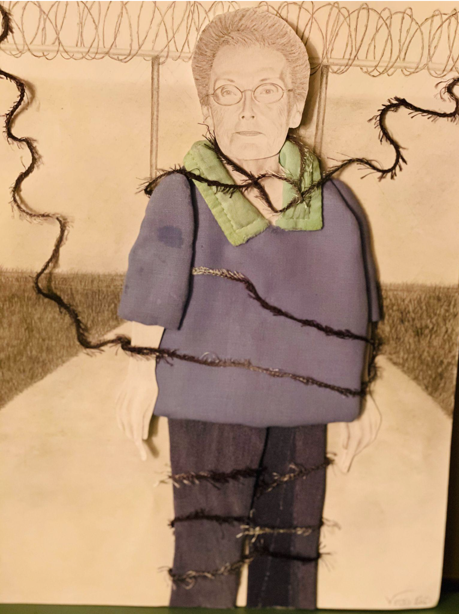 Textile display of a woman standing in front of a barbed wire fence drawn in pencil. She is wearing a purple sweater composed of fabric with a black thread wrapped around her limbs.