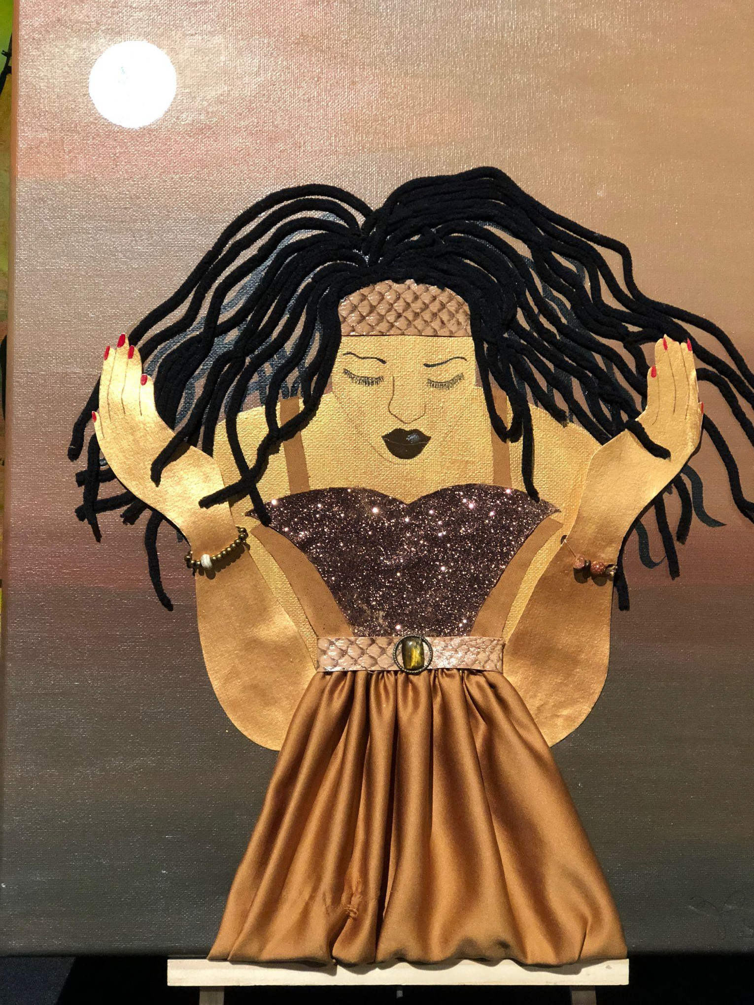 A woman with long locs kneels in prayer with her eyes closed and hands faced upwards. She is wearing a glitter top and a gold satin skirt.