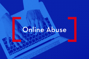 """Hands typing on a laptop; on top: """"Online Abuse"""""""